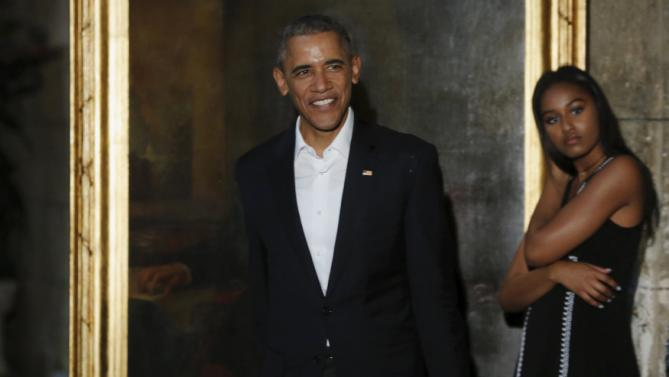 U.S. President Barack Obama smiles at reporters as he takes part in a walking tour including the Museum of the City of Havana, in Havana, Cuba March 20, 2016. Also pictured is Obama's daughter Sasha Obama (R). REUTERS/Jonathan Ernst