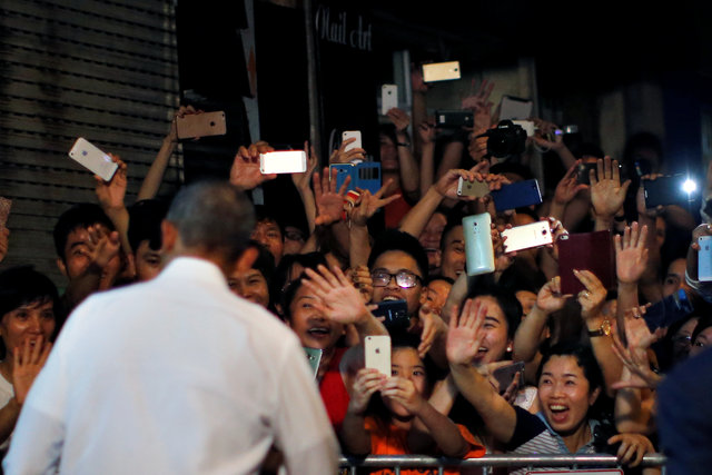 Local residents react as U.S. President Barack Obama leaves after having a dinner with Anthony Bourdain at a restaurant in Hanoi, Vietnam May 23, 2016. REUTERS/Carlos Barria