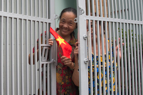 A local woman waves a flag out the door as US President Barack Obama's motorcade passes in Ho Chi Minh City on May 24, 2016. US President Barack Obama told communist Vietnam on May 24 that basic human rights would not jeopardise its stability, in an impassioned appeal for the one-party state to abandon authoritarianism. / AFP / JIM WATSON (Photo credit should read JIM WATSON/AFP/Getty Images)