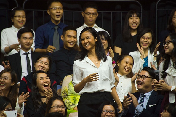 A young female rapper smiles after singing a verse to her song while asking US President Barack Obama a question at the Young Southeast Asian Leaders Initiative town hall event in Ho Chi Minh City on May 25, 2016. Obama urged communist Vietnam on May 24 to abandon authoritarianism, saying basic human rights would not jeopardise its stability, after Hanoi barred several dissidents from meeting the US leader. / AFP / JIM WATSON (Photo credit should read JIM WATSON/AFP/Getty Images)