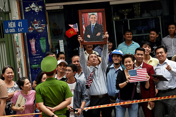 A man holds up a portrait of US President Barack Obama as people line up the streets to catch a glimpse of the US leader on his way to the airport at the end of two-day visit to Ho Chi Minh City on May 25, 2016. Obama fielded questions on May 25 on everything from rap and weed smoking to leadership and his good looks at a lively town hall-style meeting with young Vietnamese, who say the US leader is a far cry from their staid Communist rulers. / AFP / CHRISTOPHE ARCHAMBAULT (Photo credit should read CHRISTOPHE ARCHAMBAULT/AFP/Getty Images)