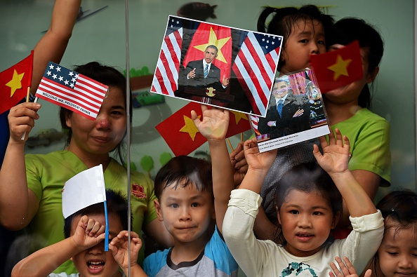 Women and children hold Vietnamese and US flags and pictures of US President Barack Obama as people line up the streets to catch a glimpse of the US leader on his way to the airport at the end of two-day visit to Ho Chi Minh City on May 25, 2016. Obama fielded questions on May 25 on everything from rap and weed smoking to leadership and his good looks at a lively town hall-style meeting with young Vietnamese, who say the US leader is a far cry from their staid Communist rulers. / AFP / CHRISTOPHE ARCHAMBAULT (Photo credit should read CHRISTOPHE ARCHAMBAULT/AFP/Getty Images)