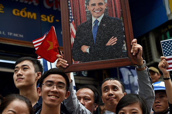 A man holds a portrait of US President Barack Obama as people line up the streets to catch a glimpse of the US leader on his way to the airport at the end of two-day visit to Ho Chi Minh City on May 25, 2016. Obama fielded questions on May 25 on everything from rap and weed smoking to leadership and his good looks at a lively town hall-style meeting with young Vietnamese, who say the US leader is a far cry from their staid Communist rulers. / AFP / CHRISTOPHE ARCHAMBAULT (Photo credit should read CHRISTOPHE ARCHAMBAULT/AFP/Getty Images)