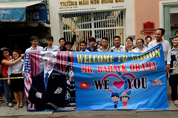 People hold a banner as they line up the streets to catch a glimpse of US President Barack Obama on his way to the airport at the end of two-day visit to Ho Chi Minh City on May 25, 2016. Obama fielded questions on May 25 on everything from rap and weed smoking to leadership and his good looks at a lively town hall-style meeting with young Vietnamese, who say the US leader is a far cry from their staid Communist rulers. / AFP / CHRISTOPHE ARCHAMBAULT (Photo credit should read CHRISTOPHE ARCHAMBAULT/AFP/Getty Images)