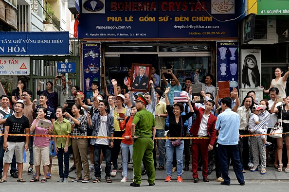 People line up the streets to catch a glimpse of US President Barack Obama on his way to the airport at the end of two-day visit to Ho Chi Minh City on May 25, 2016. Obama fielded questions on May 25 on everything from rap and weed smoking to leadership and his good looks at a lively town hall-style meeting with young Vietnamese, who say the US leader is a far cry from their staid Communist rulers. / AFP / CHRISTOPHE ARCHAMBAULT (Photo credit should read CHRISTOPHE ARCHAMBAULT/AFP/Getty Images)