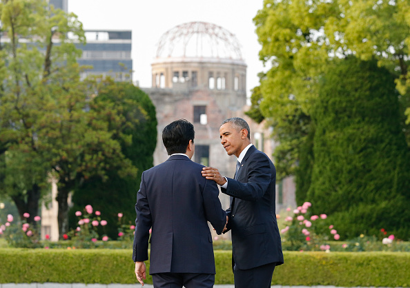 US Presdent Barack Obama (R) shakes hands with Japanese Prime Minister Shinzo Abe (L) after laying a wreath in front of the cenotaph to offer a prayer for victims of the atomic bombing in 1945 at Hiroshima Peace Memorial Park in Hiroshima on May 27, 2016. Obama on May 27 paid moving tribute to victims of the world's first nuclear attack. / AFP / POOL / KIMIMASA MAYAMA (Photo credit should read KIMIMASA MAYAMA/AFP/Getty Images)