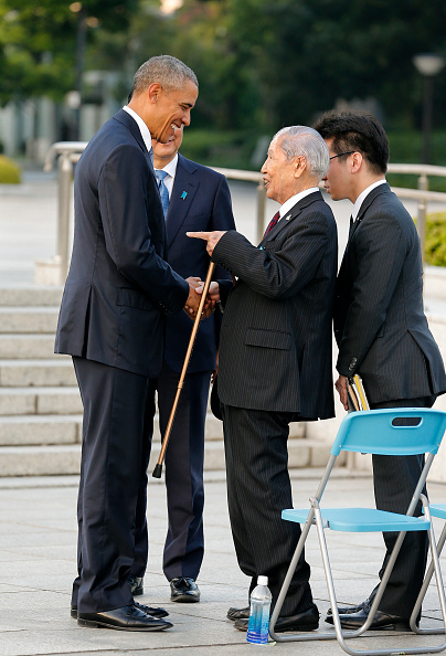 US Presdent Barack Obama (L) talks with 91-year-old A-bomb survivor Sunao Tsuboi (C) as Japanese Prime Minister Shinzo Abe (behind L) looks on, after laying a wreath in front of a cenotaph to offer a prayer for victims of the atomic bombing in 1945 at the Hiroshima Peace Memorial Park in Hiroshima on May 27, 2016. Obama on May 27 paid moving tribute to victims of the world's first nuclear attack. / AFP / POOL / KIMIMASA MAYAMA (Photo credit should read KIMIMASA MAYAMA/AFP/Getty Images)