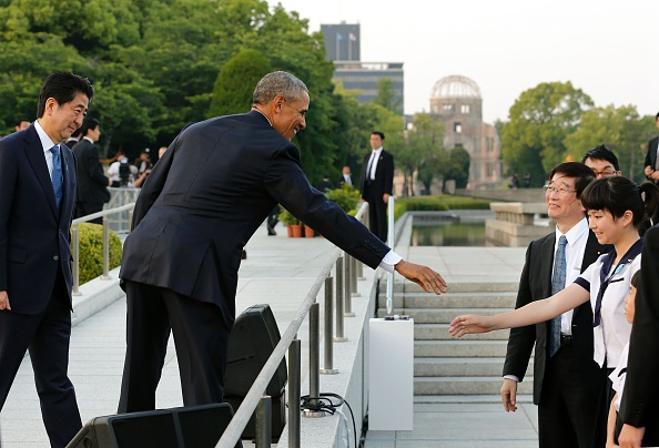 US President Barack Obama (C) greets a school student as Japanese Prime Minister Shinzo Abe watches (L) after delivering their speeches and laying wreaths in front of a cenotaph to offer a prayer for victims of the atomic bombing in 1945, at Hiroshima Peace Memorial Park in Hiroshima on May 27, 2016. Obama on May 27 paid moving tribute to victims of the world's first nuclear attack. / AFP / POOL / KIMIMASA MAYAMA (Photo credit should read KIMIMASA MAYAMA/AFP/Getty Images)