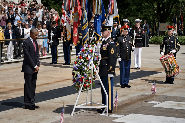 US President Barack Obama (L) bows his head after placing a wreath at the Tomb of the Unknowns to honor Memorial Day at Arlington National Cemetery May 30, 2016 in Arlington, Virginia. / AFP / Brendan Smialowski (Photo credit should read BRENDAN SMIALOWSKI/AFP/Getty Images)
