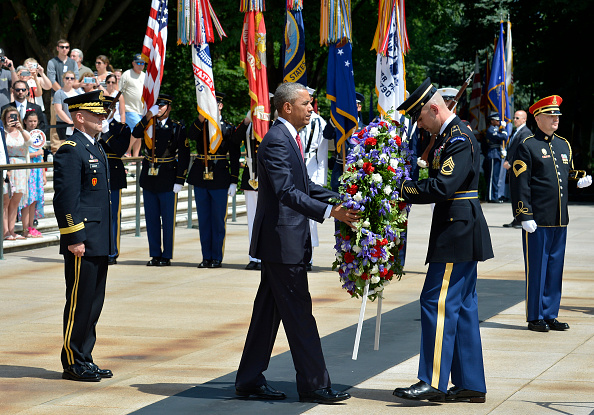 ARLINGTON, VA - MAY 30: (AFP-OUT) President Barack Obama is assisted as he lays a wreath at the Tomb of the Unknown Soldier at Arlington National Cemetery on May 30, 2016 in Arlington, Virginia. Obama paid tribute to the nation's fallen military service members. (Photo by Mike Theiler-Pool/Getty Images)