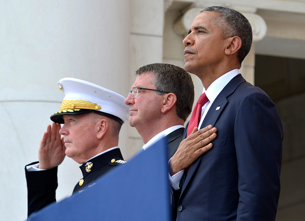 ARLINGTON, VA - MAY 30: (AFP-OUT) President Barack Obama, Chairman of the Joint Chiefs of Staff Gen. Joseph Dunford (L) and Defense Secretary Ashton Carter (C) listen to the National Anthem at the conclusion of remarks at Arlington National Cemetery on May 30, 2016 in Arlington, Virginia. Obama paid tribute to the nation's fallen military service members. (Photo by Mike Theiler-Pool/Getty Images)