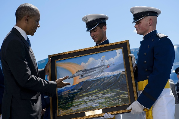US President Barack Obama is presented a painting during a graduation ceremony at the US Air Force Academy's Falcon Stadium June 2, 2016 in Colorado Springs, Colorado. / AFP / Brendan Smialowski (Photo credit should read BRENDAN SMIALOWSKI/AFP/Getty Images)
