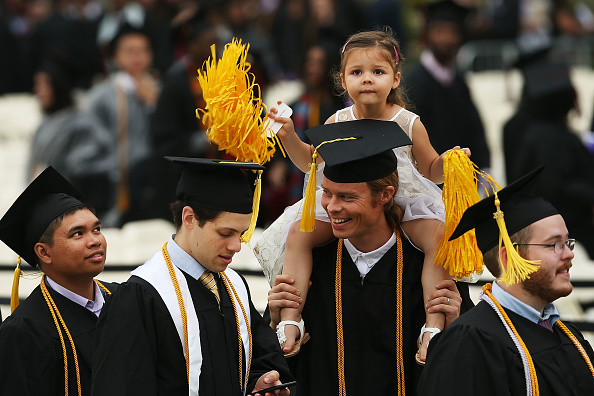 NEW YORK, NY - JUNE 03: Graduating student Kaspar Wittlinger holds his daughter Isabela during ceremonies for commencement exercises at City College on June 3, 2016 in New York City. First lady Michelle Obama delivered the commencement speech, the final commencement appearance of her tenure as first lady. In her speech Mrs. Obama celebrated City CollegeÕs diverse student body and the struggles that many students endured on the road to graduation. (Photo by Spencer Platt/Getty Images)