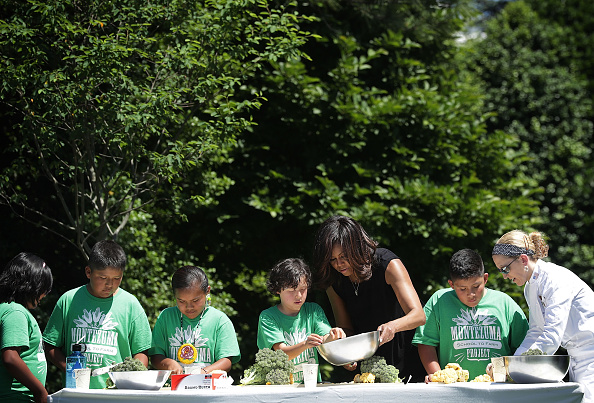 WASHINGTON, DC - JUNE 06: U.S. first lady Michelle Obama (3rd R) and Executive Pastry Chef Susan Morrison (R) prepare ingredients from a White House Kitchen Garden harvest for cooking with students June 6, 2016 at the White House in Washington, DC. The first lady welcomed back students from the kitchen garden planting earlier in spring to help the harvest today. (Photo by Alex Wong/Getty Images)