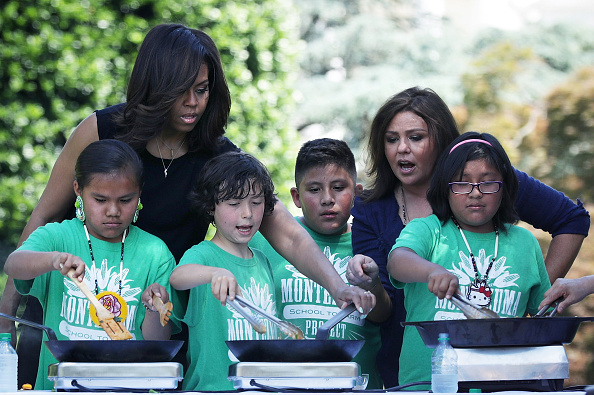 WASHINGTON, DC - JUNE 06: U.S. first lady Michelle Obama and TV host Rachael Ray cook ingredient from a White House Kitchen Garden harvest with students June 6, 2016 at the White House in Washington, DC. The first lady welcomed back students from the kitchen garden planting earlier in spring to help the harvest today. (Photo by Alex Wong/Getty Images)