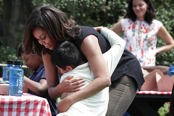 WASHINGTON, DC - JUNE 06: U.S. first lady Michelle Obama hugs a student after they participated in a White House Kitchen Garden harvest June 6, 2016 at the White House in Washington, DC. The first lady welcomed back students from the kitchen garden planting earlier in spring to help the harvest today. (Photo by Alex Wong/Getty Images)