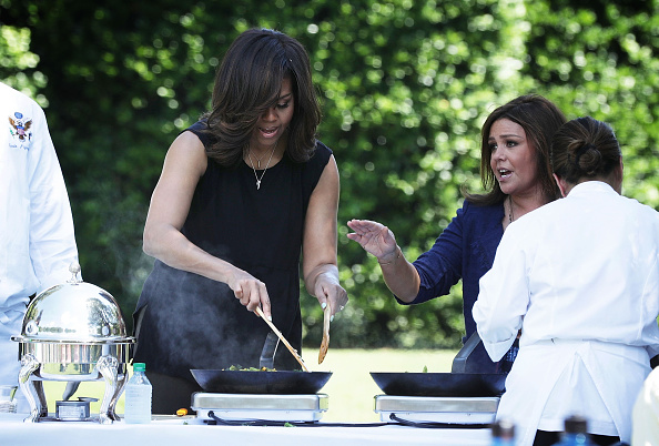 WASHINGTON, DC - JUNE 06: U.S. first lady Michelle Obama (L) and TV host Rachael Ray (R) cook ingredients from a White House Kitchen Garden harvest June 6, 2016 at the White House in Washington, DC. The first lady welcomed back students from the kitchen garden planting earlier in spring to help the harvest today. (Photo by Alex Wong/Getty Images)