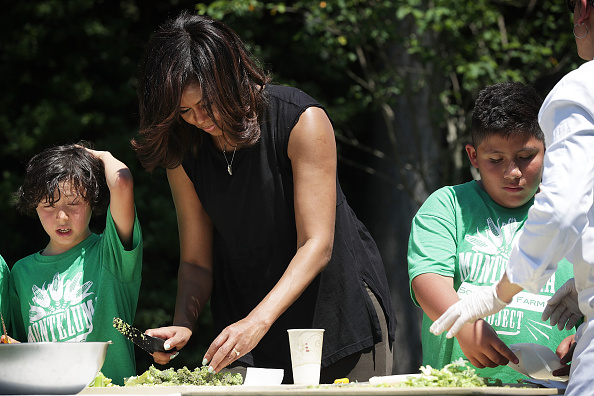 WASHINGTON, DC - JUNE 06: U.S. first lady Michelle Obama (2nd L) prepares ingredients from a White House Kitchen Garden harvest for cooking with students June 6, 2016 at the White House in Washington, DC. The first lady welcomed back students from the kitchen garden planting earlier in spring to help the harvest today. (Photo by Alex Wong/Getty Images)