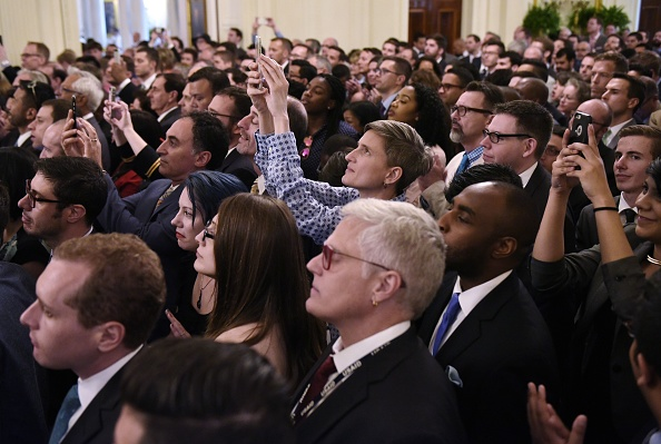 Attendees take photos as US President Barack Obama speaks during a reception to mark LGBT month in the East Room of the White House on June 9, 2016 in Washington, DC. / AFP / Mandel Ngan (Photo credit should read MANDEL NGAN/AFP/Getty Images)