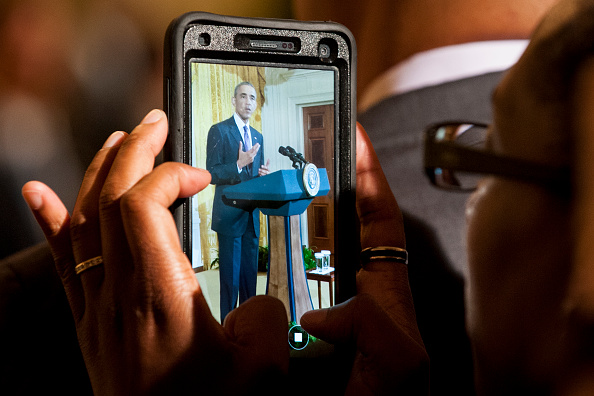 A woman photographs President Barack Obama as he delivers remarks at a reception in the East Room of the White House in recognition of LGBT Pride Month on June 9, 2016 in Washington, D.C. Photo by Pete Marovich/UPI/POOL
