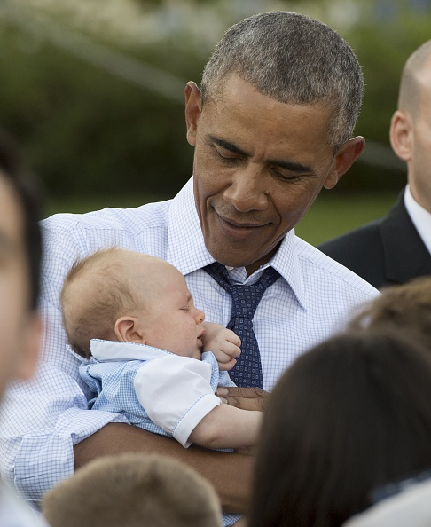 US President Barack Obama holds a baby as he greets guests during a picnic for members of Congress on the South Lawn of the White House in Washington, DC, June 14, 2016. / AFP / SAUL LOEB (Photo credit should read SAUL LOEB/AFP/Getty Images)