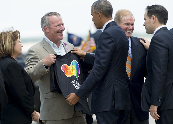 "Orlando Mayor Buddy Dyer (2nd L) holds up a ""Orlando United"" t-shirt while greeting US President Barack Obama, alongside Florida Senators Bill Nelson (2nd R) and Marco Rubio (R), after Obama arrived at Orlando International Airport in Orlando, Florida, June 16, 2016. Obama arrived Thursday in Orlando where he will console loved ones devastated by a shooting rampage that has fueled America's culture wars and a fresh push for gun controls. / AFP / SAUL LOEB (Photo credit should read SAUL LOEB/AFP/Getty Images)"