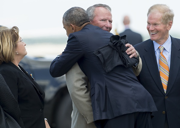 US President Barack Obama hugs Orlando Mayor Buddy Dyer (C) alongside Florida Senator Bill Nelson (R) after Obama arrived on Air Force One at Orlando International Airport in Orlando, Florida, June 16, 2016. Obama arrived Thursday in Orlando where he will console loved ones devastated by a shooting rampage that has fueled America's culture wars and a fresh push for gun controls. / AFP / SAUL LOEB (Photo credit should read SAUL LOEB/AFP/Getty Images)
