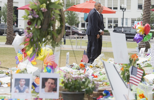 US President Barack Obama and Vice President Joe Biden pause after laying flowers for the victims of the mass shooting at a gay nightclub Sunday at a memorial at the Dr. Phillips Center for the Performing Arts in Orlando, Florida, June 16, 2016. / AFP / SAUL LOEB (Photo credit should read SAUL LOEB/AFP/Getty Images)