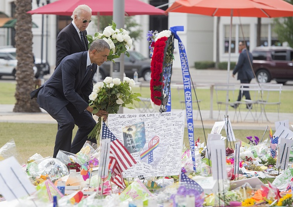 US President Barack Obama and Vice President Joe Biden lay flowers for the victims of the mass shooting at a gay nightclub Sunday at a memorial at the Dr. Phillips Center for the Performing Arts in Orlando, Florida, June 16, 2016. / AFP / SAUL LOEB (Photo credit should read SAUL LOEB/AFP/Getty Images)