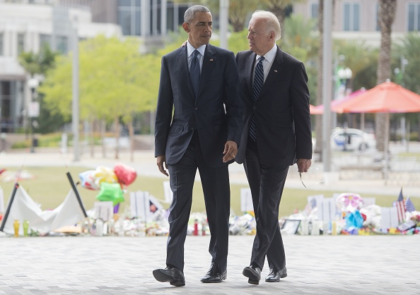 US President Barack Obama and Vice President Joe Biden walk to speak to the media after placing flowers for the victims of the mass shooting at a gay nightclub Sunday at a memorial at the Dr. Phillips Center for the Performing Arts in Orlando, Florida, June 16, 2016. / AFP / SAUL LOEB (Photo credit should read SAUL LOEB/AFP/Getty Images)