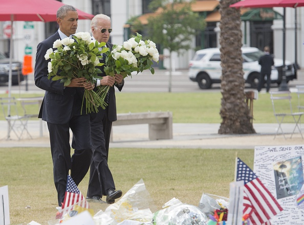 US President Barack Obama and Vice President Joe Biden place flowers for the victims of the mass shooting at a gay nightclub Sunday at a memorial at the Dr. Phillips Center for the Performing Arts in Orlando, Florida, June 16, 2016. / AFP / SAUL LOEB (Photo credit should read SAUL LOEB/AFP/Getty Images)