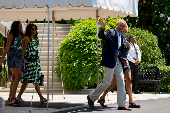 US President Barack Obama waves while walking with his daughter Malia (R), First Lady Michelle Obama (2nd L) and daughter Sasha (L) as they depart the White House in Washington, DC, June 17, 2016. The family is headed to New Mexico and California. / AFP / JIM WATSON (Photo credit should read JIM WATSON/AFP/Getty Images)
