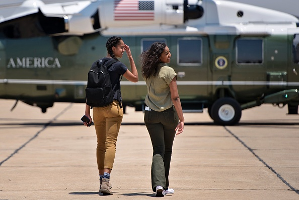 Malia Obama (L) and Sasha Obama walk to a helicopter while looking back at their parents at Roswell International Air Center June 17, 2016 in Roswell, New Mexico. / AFP / Brendan Smialowski (Photo credit should read BRENDAN SMIALOWSKI/AFP/Getty Images)