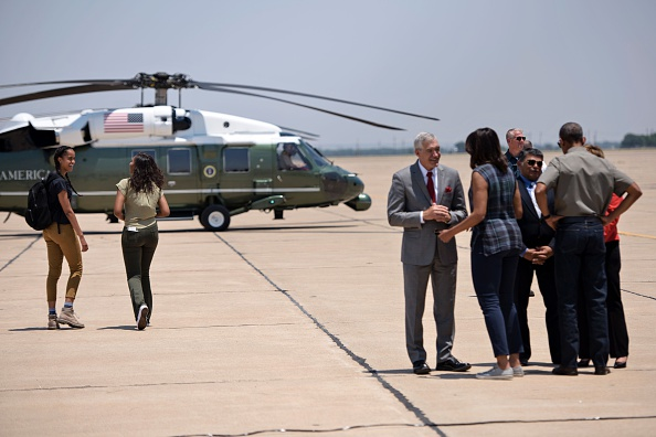 Malia Obama (L) and Sasha Obama walk to a helicopter while looking back at US First Lady Michelle Obama and US President Barack Obama as they greet officials at Roswell International Air Center June 17, 2016 in Roswell, New Mexico. / AFP / Brendan Smialowski (Photo credit should read BRENDAN SMIALOWSKI/AFP/Getty Images)