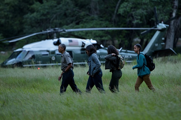 US President Barack Obama with first lady Michelle Obama and their daughters Sasha and Malia (R) walk through Ahwahnee Meadow after arriving on Marine One June 17, 2016 in Yosemite Vally, California. / AFP / Brendan Smialowski (Photo credit should read BRENDAN SMIALOWSKI/AFP/Getty Images)