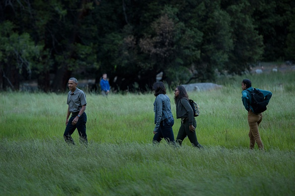 US President Barack Obama, first lady Michelle Obama an dtheir daughters Sasha Obama and Malia walk through Ahwahnee Meadow after arriving on Marine One June 17, 2016 in Yosemite Vally, California. / AFP / Brendan Smialowski (Photo credit should read BRENDAN SMIALOWSKI/AFP/Getty Images)