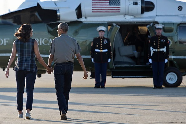 US first lady Michelle Obama and President Barack Obama walk to Marine One after arriving at Castle Airport June 17, 2016 in Merced County, California. / AFP / Brendan Smialowski (Photo credit should read BRENDAN SMIALOWSKI/AFP/Getty Images)