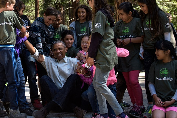 "Children help US President Barack Obama stand after he spoke to them about the ""Every Kid in the Park"" initiative while celebrating the 100th year of US National Parks, on June 18, 2016 in Yosemite Valley, California. / AFP / Brendan Smialowski (Photo credit should read BRENDAN SMIALOWSKI/AFP/Getty Images)"