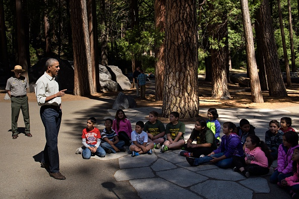 "US President Barack Obama speaks to children about the ""Every Kid in the Park"" initiative in Yosemite National Park, California, while celebrating the 100th year of US National Parks June 18, 2016. / AFP / Brendan Smialowski (Photo credit should read BRENDAN SMIALOWSKI/AFP/Getty Images)"