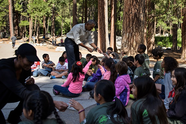 "US First Lady Michelle Obama (L) and US President Barack Obama hand out National Park passes to children for the ""Every Kid in the Park"" initiative in Yosemite National Park, California, while celebrating the 100th year of US National Parks June 18, 2016. / AFP / Brendan Smialowski (Photo credit should read BRENDAN SMIALOWSKI/AFP/Getty Images)"