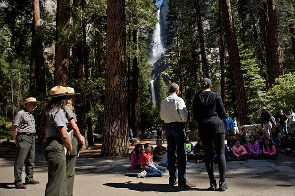 """US First Lady Michelle Obama listens while US President Barack Obama speaks to children about the """"Every Kid in the Park"""" initiative in Yosemite National Park, California, while celebrating the 100th year of US National Parks June 18, 2016. / AFP / Brendan Smialowski (Photo credit should read BRENDAN SMIALOWSKI/AFP/Getty Images)"""