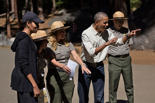 "US First Lady Michelle Obama and others listen while US President Barack Obama shows how to scare a bear while speaking to children about the ""Every Kid in the Park"" initiative in Yosemite National Park, California, while celebrating the 100th year of US National Parks June 18, 2016. / AFP / Brendan Smialowski (Photo credit should read BRENDAN SMIALOWSKI/AFP/Getty Images)"