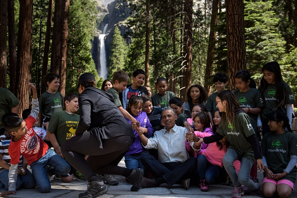 "US First Lady Michelle Obama watches as children help US President Barack Obama stand after he spoke to them about the ""Every Kid in the Park"" initiative in Yosemite National Park, California, while celebrating the 100th year of US National Parks June 18, 2016. / AFP / Brendan Smialowski (Photo credit should read BRENDAN SMIALOWSKI/AFP/Getty Images)"