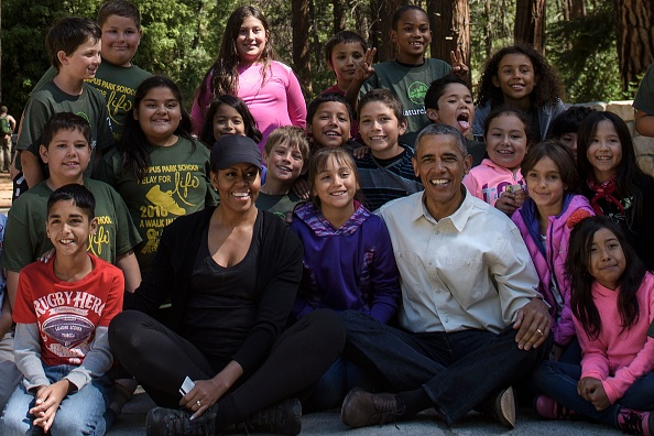 "US First Lady Michelle Obama and US President Barack Obama pose with children after speaking to them about the ""Every Kid in the Park"" initiative in Yosemite National Park, California, while celebrating the 100th anniversary of the US National Parks June 18, 2016. / AFP / Brendan Smialowski (Photo credit should read BRENDAN SMIALOWSKI/AFP/Getty Images)"
