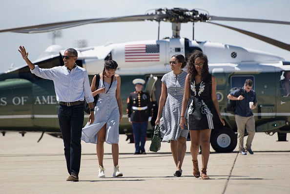 From left: US President Barack Obama, daughter Malia Obama, US first lady Michelle Obama, and daughter Sasha Obama walk to Air Force One at Castle Airport June 19, 2016 in Merced County, California. / AFP / Brendan Smialowski (Photo credit should read BRENDAN SMIALOWSKI/AFP/Getty Images)