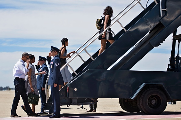 From left US: President Barack Obama, US first lady Michelle Obama, daughters Malia Obama and Sasha Obama board Air Force One at Castle Airport June 19, 2016 in Merced County, California. / AFP / Brendan Smialowski (Photo credit should read BRENDAN SMIALOWSKI/AFP/Getty Images)