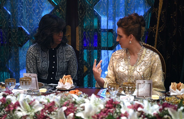 """US first lady Michelle Obama (L) speaks with Princess Lalla Salma of Morocco (R) during a dinner in Marrakech, on June 28, 2016. US First Lady Michelle Obama launched a $100 million aid package in Morocco on June 28, 2016 to promote the education of girls in a country where half of females over 15 are illiterate. Visiting Marakech with actresses Meryl Streep and Frieda Pinto of the """"Slumdog Millionaire"""" film, she told girls in attendance she wanted them to be part of a global conversation on female education. / AFP / FADEL SENNA (Photo credit should read FADEL SENNA/AFP/Getty Images)"""