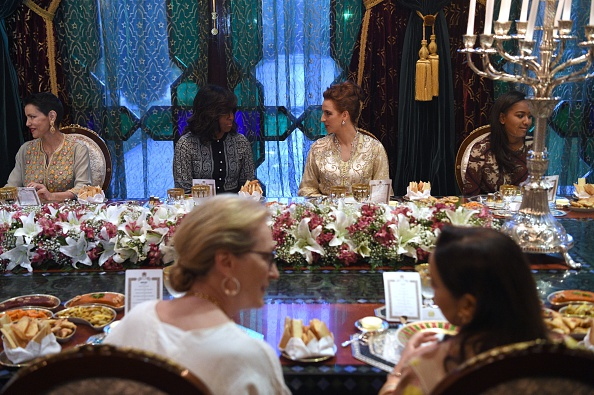 """US first lady Michelle Obama (C-L) speaks with Princess Lalla Salma of Morocco (C-R) during a dinner in Marrakech, on June 28, 2016. US First Lady Michelle Obama launched a $100 million aid package in Morocco on June 28, 2016 to promote the education of girls in a country where half of females over 15 are illiterate. Visiting Marakech with actresses Meryl Streep and Frieda Pinto of the """"Slumdog Millionaire"""" film, she told girls in attendance she wanted them to be part of a global conversation on female education. / AFP / FADEL SENNA (Photo credit should read FADEL SENNA/AFP/Getty Images)"""