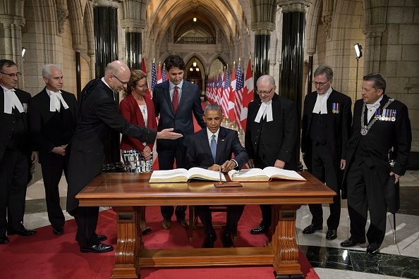 Canadian Prime Minister Justin Trudeau and others watch as US President Barack Obama signs a guest book at Parliament Hill during the North American Leaders Summit on June 29, 2016 in Ottawa, Ontario. / AFP / Brendan Smialowski (Photo credit should read BRENDAN SMIALOWSKI/AFP/Getty Images)