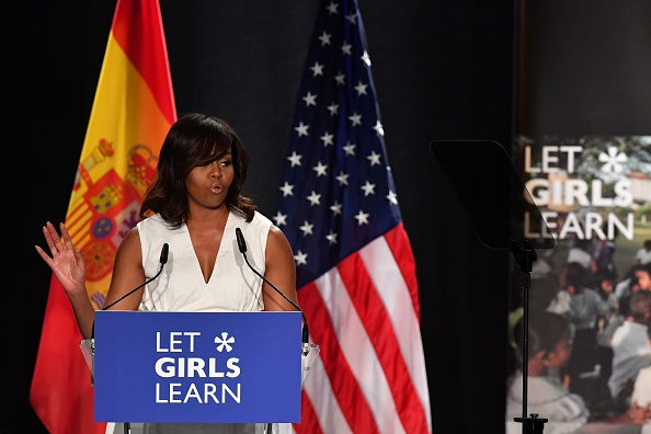 """US first lady Michelle Obama gestures as she delivers a speech presenting the """"Let Girls Learn"""" initiative on June 29, 2016 in Madrid. US First Lady Michelle Obama began a two day visit to Spain by delivering a speech on the education initiative launched in March 2015 to help adolescent girls across the world access a quality education. / AFP / GERARD JULIEN (Photo credit should read GERARD JULIEN/AFP/Getty Images)"""